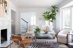 Chic, sun filled living room features an ivory linen sofa facing a square lucite cocktail table placed atop a white and black zebra rug layered atop a gray bound sisal rug.