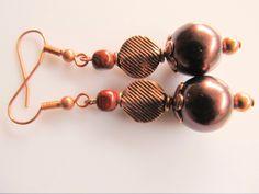 Oorbellen Copper Brown Pearl donkerbruine glasparel met een koperen muntkraal en een rode jaspis nugget kraal. geheel koper