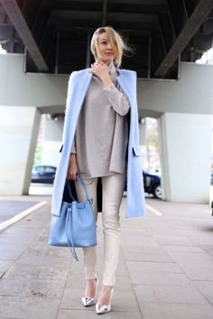 Light blue coat over a neutral outfit with a handbag to match
