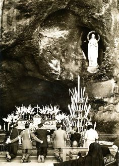 Pilgrims in prayer before the grotto of the apparitions in Lourdes, France.