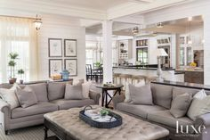 A coffered ceiling and exposed support columns are used to delineate areas in the great room, where the living area's Ralph Lauren Macintyre sofas covered in durable Belgian linen couple with a custom ottoman by Bausman & Company upholstered