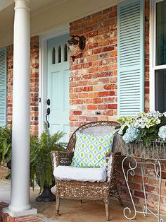 Shutters and a front door painted in a pale aqua hue create a different look and feel for this home. No longer does it feel like a 1970s ranch; instead it looks like a little cottage, which is a reflection of its interior.