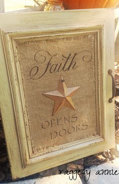 """Rusty old handle was added to the side… and coffee st… Repurposed Cabinet Door. Rusty old handle was added to the side… and coffee stained burlap to the center along with a prim star. """"Faith Opens Doors"""" was hand stenciled as a fi Cabinet Door Crafts, Old Cabinet Doors, Old Cabinets, Old Doors, Cupboards, Burlap Crafts, Wood Crafts, Repurposed Furniture, Diy Furniture"""