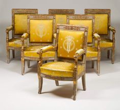 """An Empire set of six fauteuils and one settee Painted and gilt carved wood depicting dolphins,flowers and other floral motifs Green and gilt silk upsholstered seats, backs and arms Bearing """"JACOB"""" stamps France, Early 19th century"""
