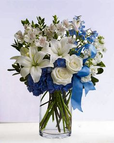 Blue floral arrangement. White roses, lilies, carnations and orchids mixed with some belladonna blue delphiniums. Stargazer lilies are my favorite<3