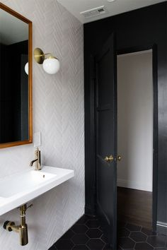 I love the idea of the black paint at and around the door. Will go well with my bathroom colors, too. bathroom renovation // herringbone tile // brass fixtures // sarah sherman samuel