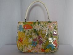 Super cute flowered handbag from the 60s. The floral design on the front of the bag is embellished with straw stitching in vibrant colors. The entire bag is covered in see through vinyl. White plastic vinyl handle. There are 3 compartments inside the bag. A middle, front and back. Tag inside reads Soure Bag New York. The overall condition of the bag is very good except for the inside lining does have some discoloration due to age and is coming apart at the sides. HEIGHT: 6 1/4 BASE: 8 MO...