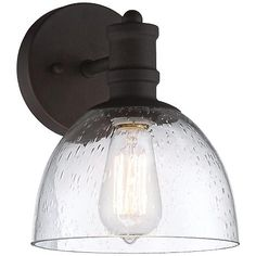 The warm bronze finish on this industrial style wall sconce gives it an authentic vintage look. A clear seedy glass shade shows off the included Nostalgic Edison style bulb.