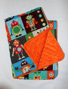 Colorful and Bright Robots Make This Orange Dot Minky Stroller Blanket Irresistible.  Orange Minky backed with a super cute robot cotton print.