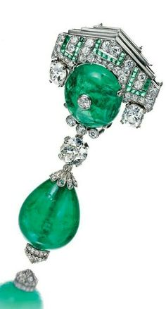 Emerald and diamond brooch. Centring on a circular cabochon emerald, the geometric surmount set with circular- and single-cut diamonds and calibré-cut emeralds, suspending two cushion-shaped diamonds and a circular-cut stone, terminating on an emerald drop, capped by rose-cut diamonds, French assay and maker's marks, fitted case.