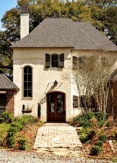 Yes!!! creamy stucco color, reddish-brown brick and door, brick pavers and dark green shutters