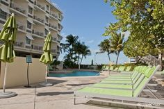 Pool area with umbrellas and colorful lime green lounge chairs. #keywesthotel #hyattkeywest #placestostay #travelideas
