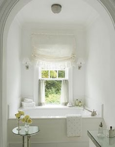 Built-in tub archway in white bathroom.