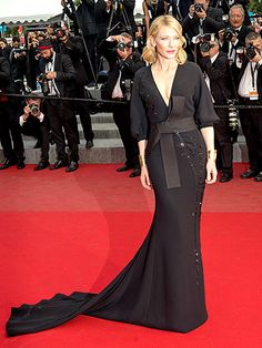 Cate Blanchett at the red carpet premiere of Sicario wore a long-sleeve black wrap dress with a plunging neckline and elaborate band cinched at her waist during the 68th annual Cannes Film Festival on May 19.