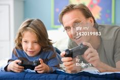 Stock Photo : Caucasian father and son playing video game