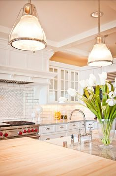 The main island has Butcher block counters and a farmhouse sink. I really like the white subway tile with an inset of marble herringbone mosaic tile.  The island lights are the Haverhilll Pendant from Hudson Valley Lighting.