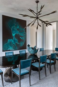 Dining Room Drama.  Glossy black dining table, blue velvet dining chairs, sculptural chandelier, large scale abstract art.