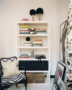 Eclectic Modern Bookshelf: A black chair with a zebra-print cushion beside a white bookshelf.