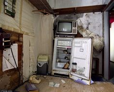 Home sweet home: A television sits precariously on top of a fridge in what was once somebody;s kitchen