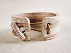 Bracelet imitation bois clair en pâte polymère Fimo, dans un style contemporain dinspiration ethnique. Les couleurs dominantes sont beige, sable et ivoire. Il mesure 2,6 cm de hauteur et 17 cm à lintérieur (pour poignets de 15 à 17 cm environ). Un bouton bâton assorti, attaché par un gros élastique beige, se glisse dans une ouverture ronde. La pâte polymère présente une certaine souplesse, et rend lenfilage très facile. Poids 26 grammes, épaisseur 4 mm. Vernis de protection satiné à…