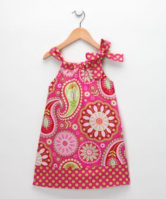 Girls with a bright sense of adventure find a happy home in this dress that comes in a vibrant mix of prints. Featuring a single tie, the neckline cinches in or out to create a look that's fun and comfortable for little ones to sport on afternoon outings.
