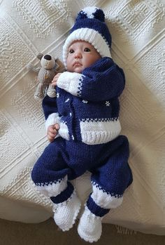 "Hand knitted reborn baby doll or newborn baby full outfit. Set includes trousers, matching cardigan, booties and hat and comes on hanger. Made with sparkling navy and white.   Made with snow style buttons which also adorn the front of the cardigan.  This is a one off outfit as I never make two the same. This is on the ""buy now "" option.  The display doll is 20"" ( NFS ).  I post all items 2nd class recorded. 