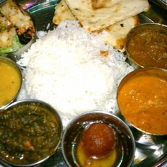Thali - Nirvana: includes, Chicken Tikka Lababdar, Lamb Curry, Frontier Garlic Shrimp, Spinach with cheese or Tofu, Lentil of the day, Naan, Basmati or Brown Rice, Dessert of the day