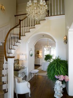 Country French Foyer - Elegant and dressy, with just the right rustic touch in the exposed stone wall beyond...
