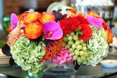 Colorful flower arrangement of green hydrangea, orange roses and celosia, green grapes, pink calla lilies, cymbidium orchid by The Empty Vase Florist #flowerarrangement  #grapes #color