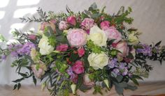 A registrars arrangement featuring pink Sarah Bernhardt Peonies, ivory and pink roses and lilac stocks.