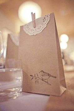 What a cute idea for a backyard wedding...paper bags imprinted with birds in black and you could use a paper or cloth doily and a clothespin with the names written on the clothespin, and the date, and then dill it with a cupcake or whatever. If you use a cloth doily it can be the favor! Beautiful!