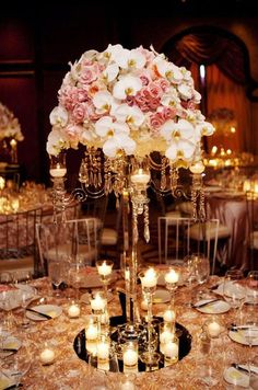 Tall centerpieces of orchids and roses are surrounded by soft, inviting candlelight. Wedding Centerpieces, Flowers, Floral Arrangements