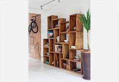Caixotes de madeira formam a estante feita sob medida por um marceneiro. Pelos nichos, distribuem-se livros e objetos pessoais. Projeto da arquiteta Rachel Nakata