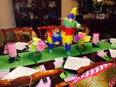 Piñata centerpiece; flowers in tomato cans; pink chevron candles