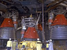 Installation of F-1 engines to the Saturn V S-IC Stage. The nozzle extension is absent from the engine being fitted.