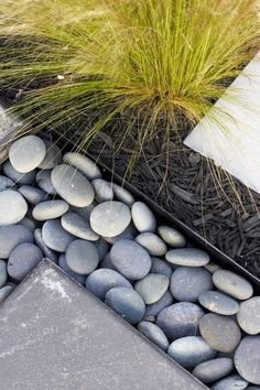 River stones used as an accent with a metal edge adds visual interest to an otherwise simple setup. The metal edging keeps the stones from spilling over into the landscape, and it also keeps the landscape from crossing over onto the pathway.