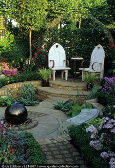 love the brick hardscape design in this small garden and the chairs are fun with a carved heart