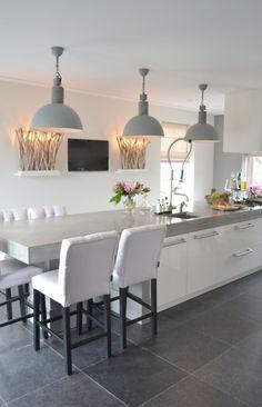 Stoere keuken met wandlampen van puur hout. De gecapitonneerde krukken geven een mooi contrast met het strakke betonnen blad, door ons gerealiseerd. Ginterieur in Amerongen