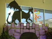 Shelf Mouse blog - our middle school campus themes were medieval, so the library obliged. The castle is  a loft bed wrapped in purple paper. The stones were made by laying cardboard templates on the paper and spray-painting around the edges to make a grout look.