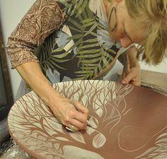 Natalie sgraffito carving a thrown porcelain platter ~ carving away the iron oxide to reveal a beautiful tree . . .