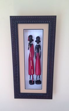 "Wood Carvings in Shadow Box Frame - Maasai Man and Woman: Two carved sculptures of a Maasai Man and Woman ""dressed"" in traditional red clothing adorned with silver jewelry and mounted in a shadow box frame."