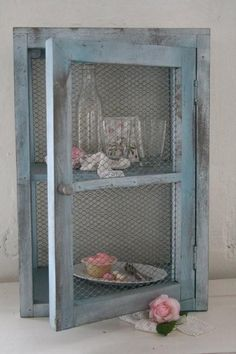 shabby chic..I think they used to call these things cake safes. No cake is safe around me! Personally, I would have fitted the background with corkboard covered in fabric and use it to organize necklaces.