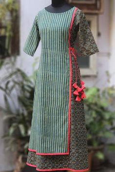 an a-line dress with front & back flap & tie-ups with fabric tokri on one side! Simple Kurti Designs, Kurta Designs Women, Kurti Neck Designs, Dress Neck Designs, Salwar Designs, Blouse Designs, Latest Kurti Designs, Batik Dress, Indian Designer Wear