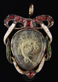 Martha Washington's mourning jewelry. On the death of George Washington in 1799 she had a snippet of his hair put in this locket. When she died a snippet of her hair was added. Mourning jewelry was a...