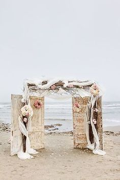 Use reclaimed driftwood to create a custom altar for your beach wedding. White tulle and flowers will make it the perfect backdrop to your ceremony.