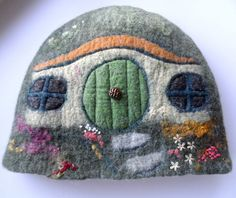 This is my hobbit-hole teapot cosy.. seamlessly wet-felted (no sewing or knitting involved!) from white English wool fibre and coloured merino wool fibres. I have used lots of stitching, both freemotion machine, and hand embroidery to define and decorate Bag End.    I used white English wool fibre for the inside and coloured merino fibre for the outside, adding curly wool locks, silk fibres and wool nepps to the final layers creating a textural, colourful hillside.    Size:  Outside…
