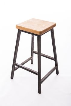 Low bar stool, industrial style made with steel square tube and English oak seat.I can make seats in any wood type. Raw steel finished with beeswax. Powder coating available in pretty much any colour you like.Optional heights. Feet have plastic inserts so that they don't damage floors