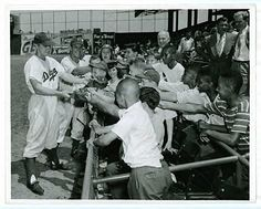 Pee Wee Reese signing autographs for the fans at Ebbets Field.