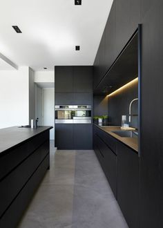 kitchen idea - M House is a minimalist house located in Melbourne, Australia, designed by DKO. The kitchen space features blacked out custom cabinetry with a black kitchen island that allows for seating and serving. Kitchen Ikea, Modern Kitchen Cabinets, New Kitchen, Kitchen Dining, Kitchen Gadgets, Kitchen Modern, Awesome Kitchen, Kitchen Layout, Kitchen Contemporary