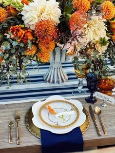 .Autumn inspired tablescape. Orange flowers, bright blue sapphire, jewel tones, gold, elegant, rustic